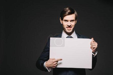 Photo pour Homme d'affaires gai pointer avec le doigt au plateau vide isolé sur dos - image libre de droit