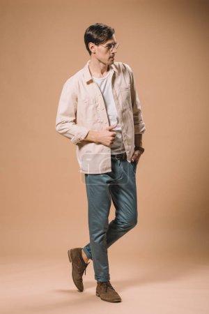 Photo pour Homme confiant dans des lunettes debout avec la main dans la poche sur fond beige - image libre de droit