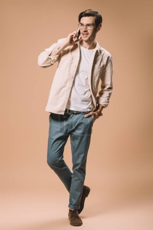 happy man in glasses talking on smartphone while standing with hand in pocket on beige  background