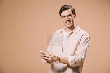 Photo for Cheerful man in glasses holding smartphone and smiling isolated on beige - Royalty Free Image