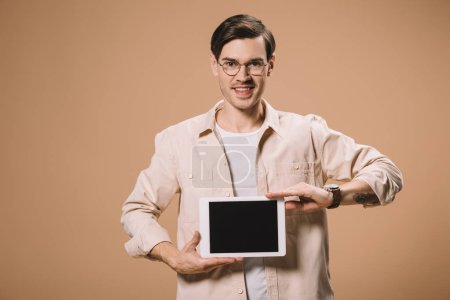 smiling man in glasses holding digital tablet with blank screen isolated on beige