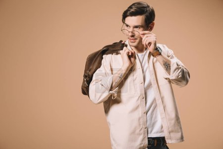 Photo for Handsome man touching glasses while standing with bag isolated on beige - Royalty Free Image