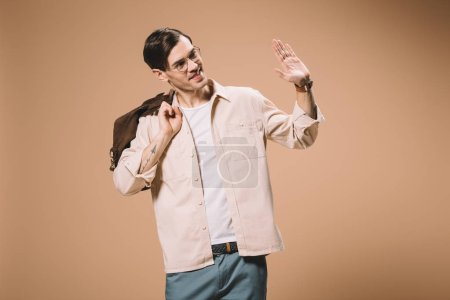 handsome man in glasses waving hand while holding bag isolated on beige