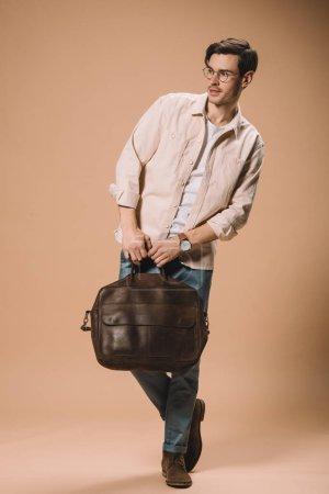 Photo pour Bel homme dans des lunettes tenant sac sur fond beige - image libre de droit
