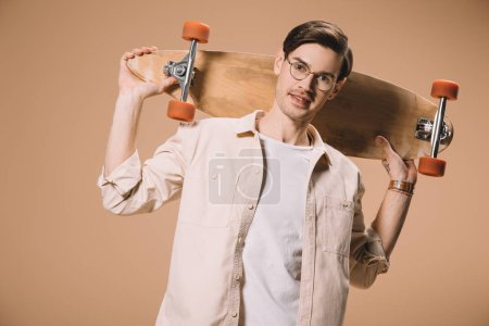 cheerful man in glasses holding skateboard while standing  isolated on beige
