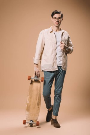 Photo for Confident man in glasses holding skateboard while standing on beige  background - Royalty Free Image
