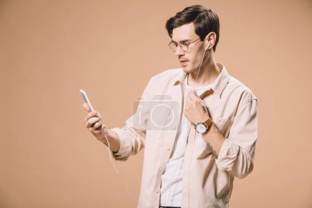 handsome man in glasses looking at smartphone while listening music in earphones  isolated on beige