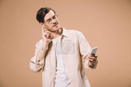 Photo pour Bel homme à lunettes tenant smartphone et écoutant de la musique dans des écouteurs avec les yeux fermés isolés sur beige - image libre de droit