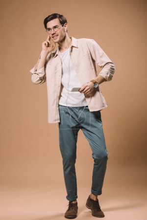 Photo pour Bel homme en lunettes tenant smartphone et écouteurs touchants sur fond beige - image libre de droit