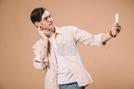 handsome man in glasses looking at smartphone while listening music isolated on beige