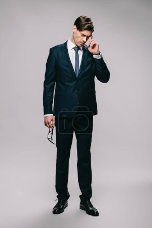 Photo for Handsome businessman standing in suit and holding head on grey background - Royalty Free Image