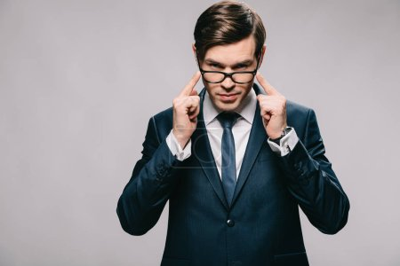 Photo for Confident businessman holding glasses while standing in suit isolated on grey - Royalty Free Image