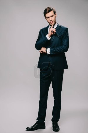 thoughtful businessman standing in suit on grey background