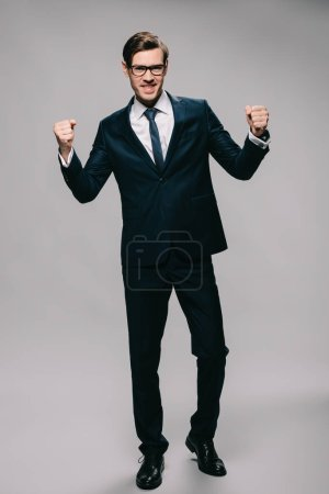 Photo for Happy businessman celebrating victory while standing on grey background - Royalty Free Image