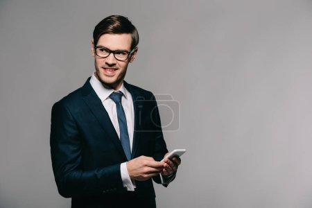 Photo for Cheerful businessman using smartphone while standing in suit on grey background - Royalty Free Image