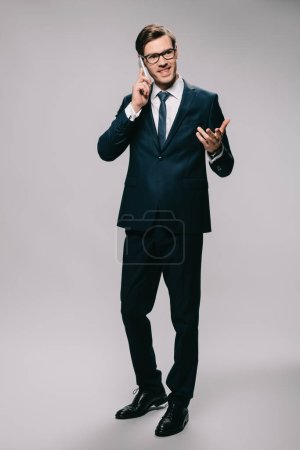 Photo for Cheerful businessman talking on smartphone while standing in suit on grey background - Royalty Free Image
