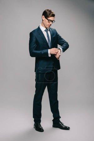 Photo for Confident man in suit looking at watch on grey background - Royalty Free Image
