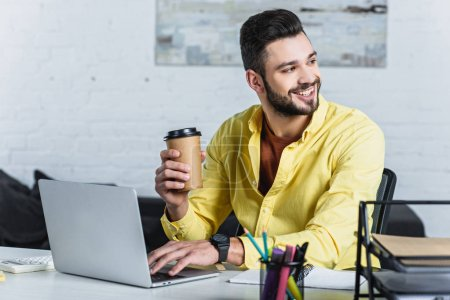 Photo for Smiling businessman holding paper cup, using laptop and looking away - Royalty Free Image