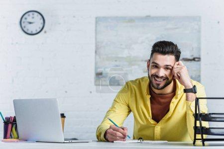 Photo pour Homme d'affaires gai tenir crayon, touchant la tête et regarder la caméra - image libre de droit