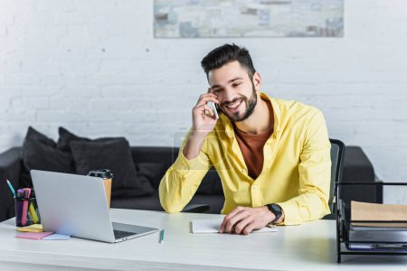 Smiling bearded businessman talking on smartphone at office