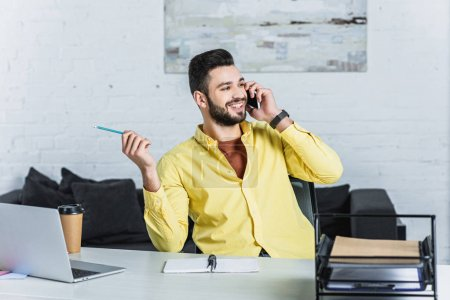 Cheerful bearded businessman holding pencil and talking on smartphone