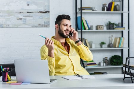 Cheerful bearded businessman talking on smartphone and looking away