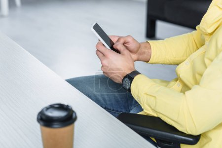 Photo for Partial view of man holding smartphone at workplace - Royalty Free Image