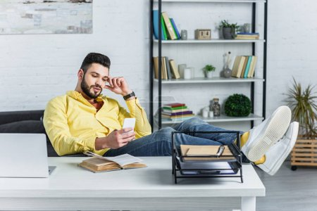Photo for Thoughtful bearded businessman in yellow shirt looking at smartphone at workplace - Royalty Free Image