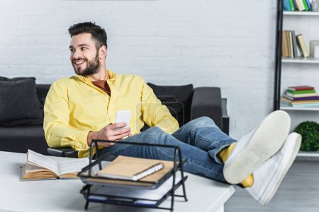 Smiling bearded businessman holding smartphone and looking away