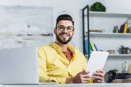Cheerful businessman in glasses looking at camera at office