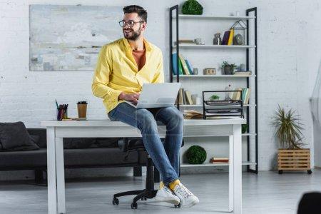 Foto de Barbudo hombre de negocios en vasos escribir, sentado en el escritorio y mirando lejos - Imagen libre de derechos