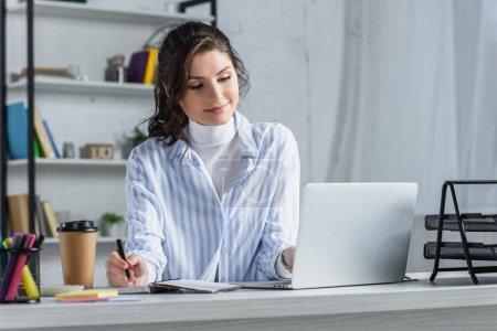Photo pour Sourire attrayant femme d'affaires écrivant dans un cahier au bureau - image libre de droit