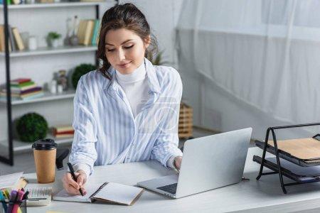 Photo pour Sourire belle femme d'affaires écrit dans un cahier sur le lieu de travail - image libre de droit