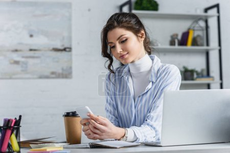 Attractive businesswoman holding smartphone and typing at workplace