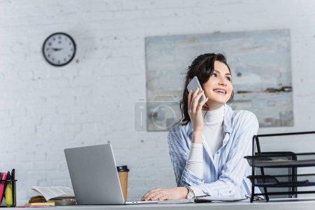 Photo pour Belle femme d'affaires parler sur smartphone et en regardant loin de bureau - image libre de droit