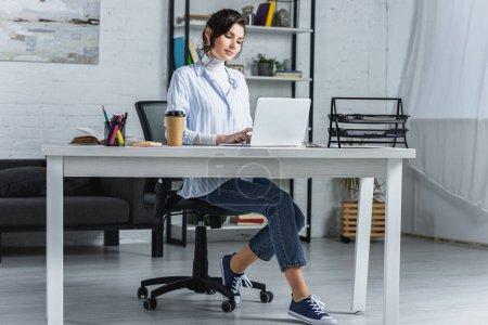 Photo pour Attrayant femme tapant sur ordinateur portable dans le bureau moderne - image libre de droit