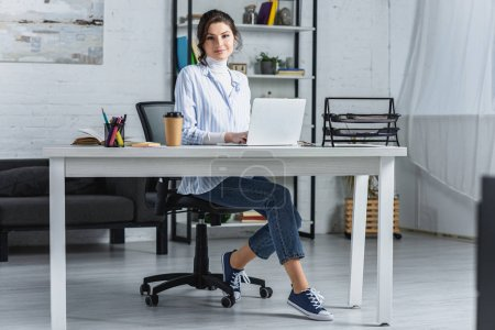 cheerful woman using on laptop while sitting in modern office