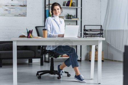 Photo pour Femme joyeuse utilisation sur ordinateur portable assis dans le bureau moderne - image libre de droit