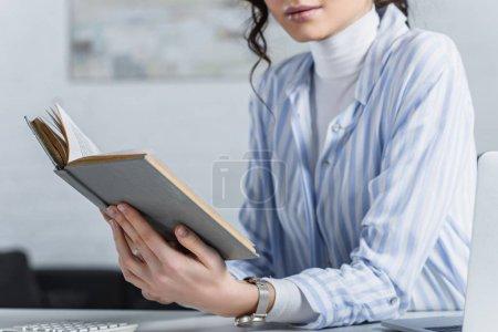 Foto de Vista recortada de estudiar con el libro en la oficina de la mujer - Imagen libre de derechos