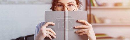 Photo pour Femme en lunettes couvrant visage avec livre - image libre de droit