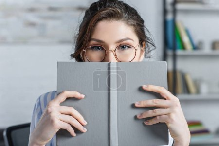 Photo for Woman in glasses covering face with book in modern office - Royalty Free Image