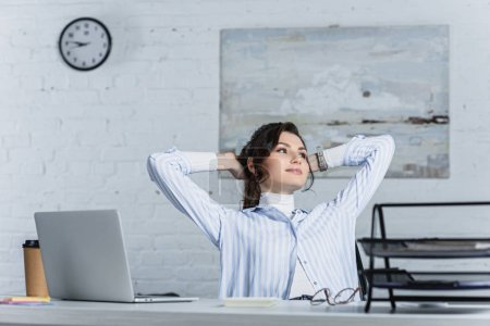 thoughtful woman sitting near laptop in modern office
