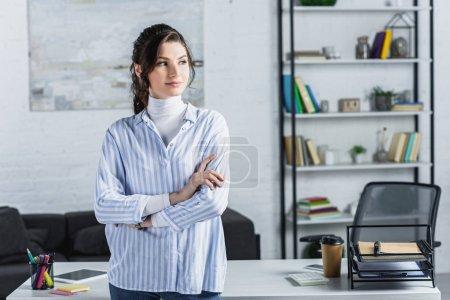 Photo pour Belle femme debout avec les bras croisés dans le bureau moderne - image libre de droit
