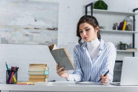 Photo pour Femme triste étudiant avec le livre tout en tenant la plume dans la main dans le bureau moderne - image libre de droit