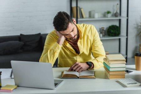 Foto de Hombre cansado de estudiar con el libro cerca de laptop en la oficina moderna - Imagen libre de derechos