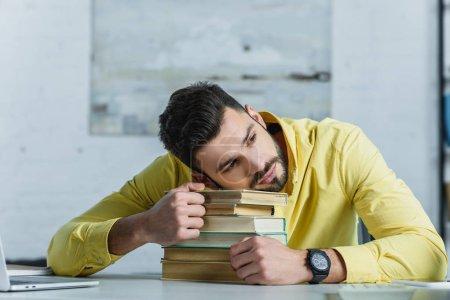 Photo pour Homme fatigué se trouvant sur les livres dans le bureau moderne - image libre de droit
