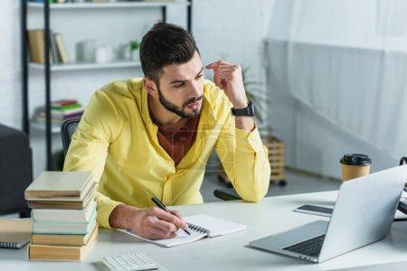 Foto de Hombre guapo de la escritura en el cuaderno y mirando la laptop en la oficina moderna - Imagen libre de derechos