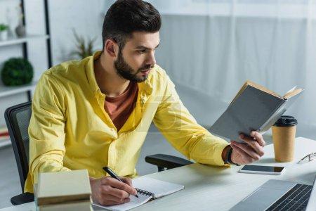 Foto de Hombre guapo con libro y ordenador portátil en la oficina moderna - Imagen libre de derechos