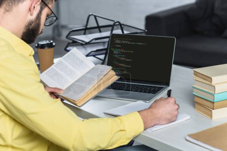 Photo for Bearded man studying with book near laptop with computer coding on screen in modern office - Royalty Free Image