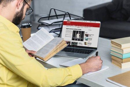 Photo pour Barbu homme étudier avec livre près ordinateur portable avec bbc site à l'écran dans le bureau moderne - image libre de droit